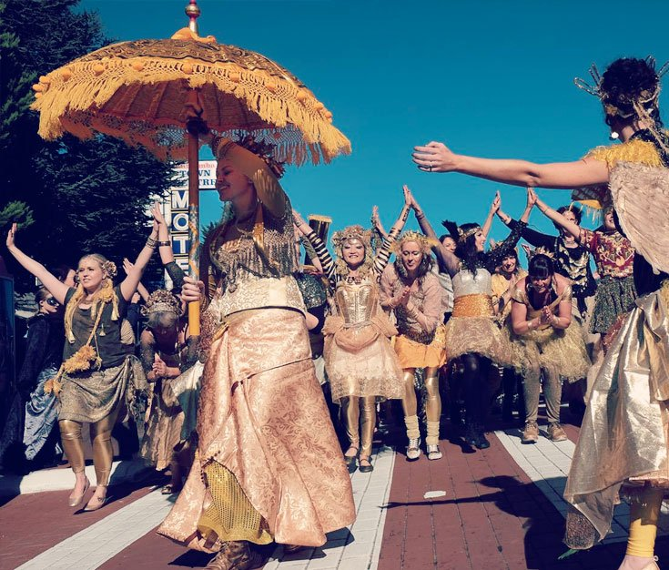 Dancers at parade starting line, Elaborately dressed in gold with big gold parasol