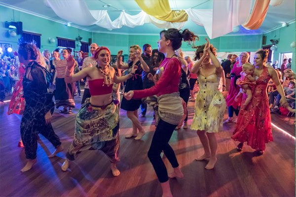Colourful image of people dancing and smiling, lovey billows of fabric decorating the ceiling
