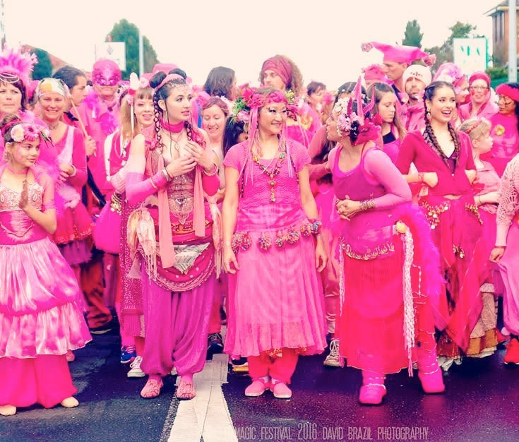 large group of dancers in elaborate bright pink costumes in a line, smiling, getting ready